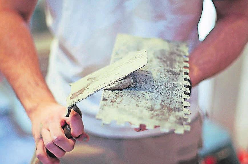 Auf den Kleber kommt es an: Während ihrer Ausbildung lernen Fliesenleger unter anderem, wie Fliesen und Kacheln auf verschiedenen Böden am besten halten.